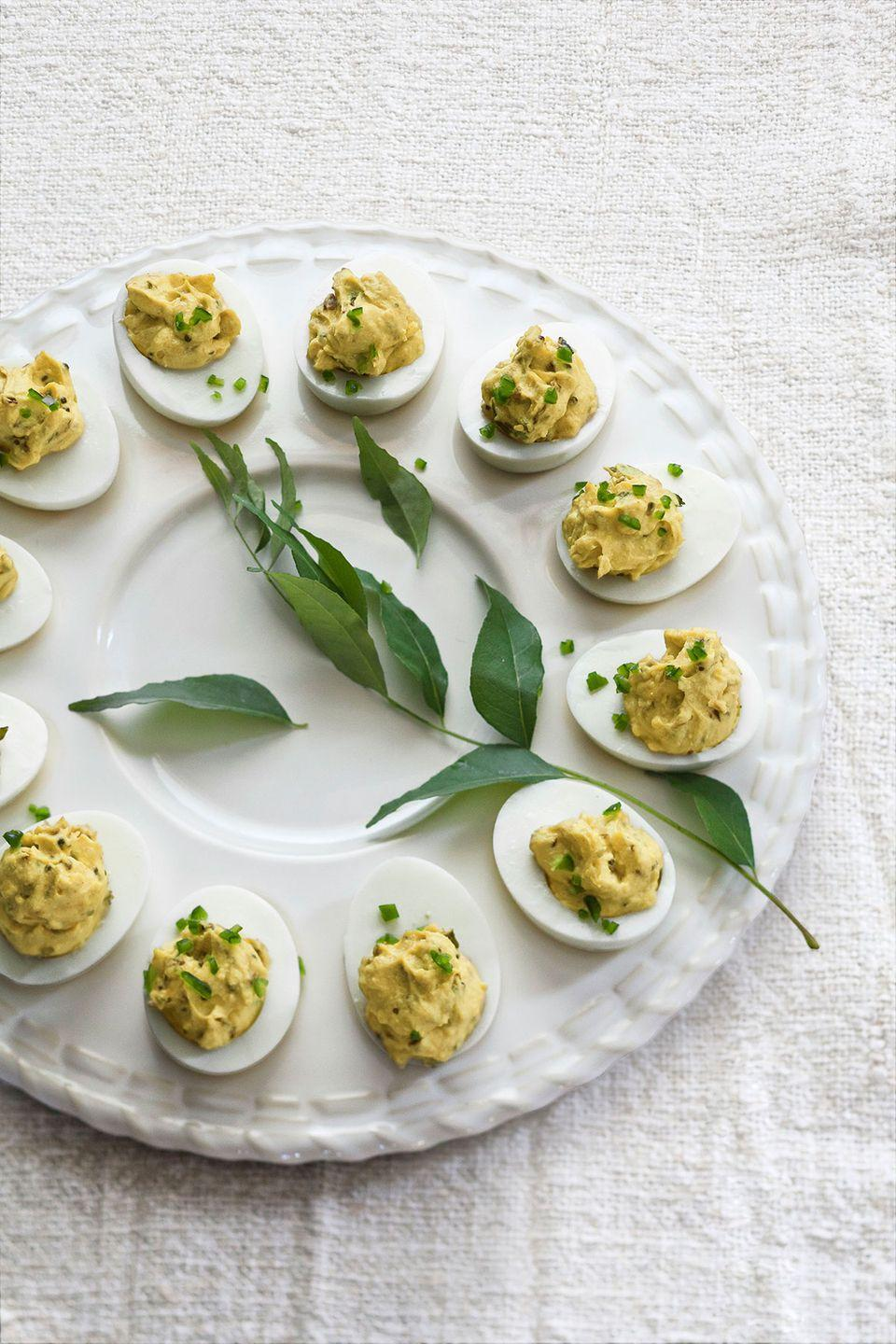 "<p>If you love Indian food and curry, then you won't be able to resist these deviled eggs with an extra kick.</p><p><strong><a href=""https://www.countryliving.com/food-drinks/recipes/a4205/deviled-eggs-cilantro-jalapenos-curry-recipe-clv0712/"" rel=""nofollow noopener"" target=""_blank"" data-ylk=""slk:Get the recipe"" class=""link rapid-noclick-resp"">Get the recipe</a>.</strong></p>"