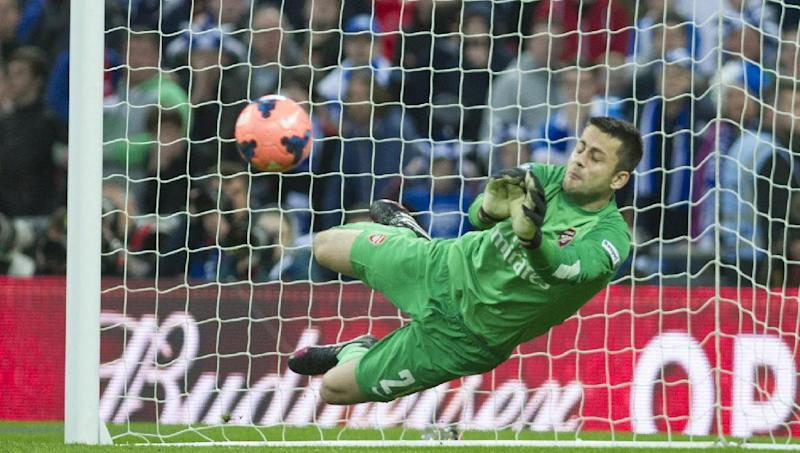 CAPTION CORRECTION, CORRECTS ID OF GOALKEEPER - Arsenal's Lukasz Fabianski, makes a save against Wigan Athletic, during their English FA Cup semifinal soccer match, at the Wembley Stadium in London, Saturday, April 12, 2014