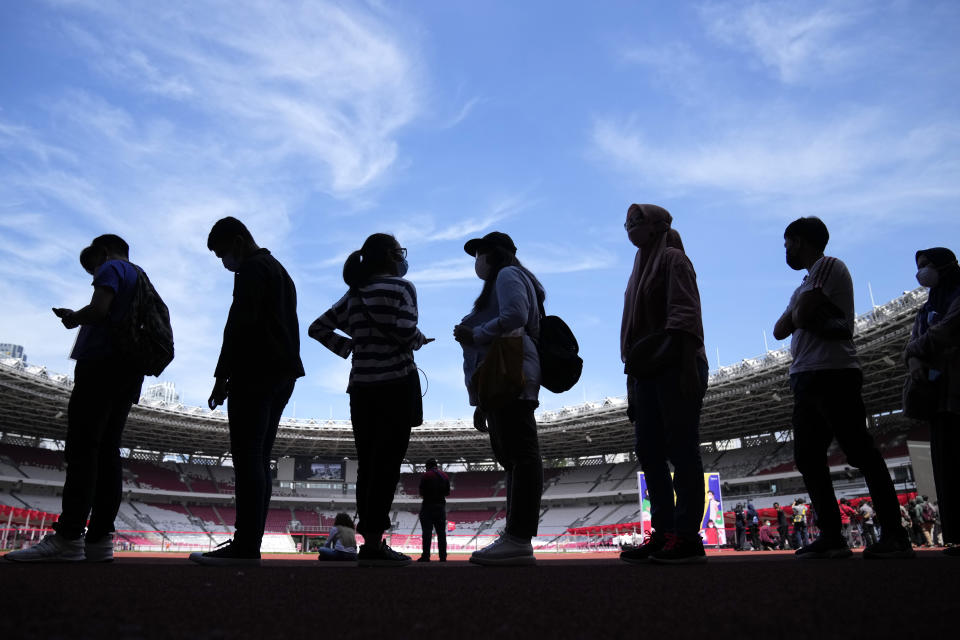 People are silhouetted against the sky as they line up to get the Sinovac COVID-19 vaccine during a mass vaccination at Gelora Bung Karno Main Stadium in Jakarta, Indonesia, Saturday, June 26, 2021. The world's fourth most populous country, has seen COVID-19 infections surge in recent weeks, putting pressure on hospitals, including in the capital city, where most of hospital beds are full, and has added urgency to the government's plan to inoculate 1 million people each day by next month. (AP Photo/Dita Alangkara)