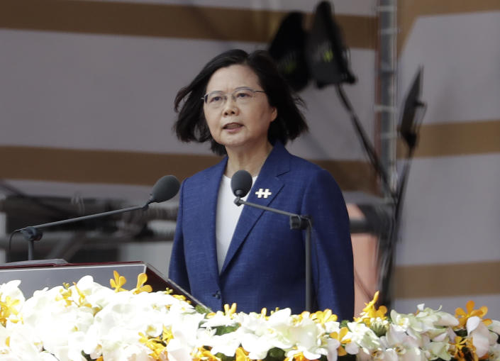 FILE - In this Oct. 10, 2021, file photo, Taiwanese President Tsai Ing-wen delivers a speech during National Day celebrations in front of the Presidential Building in Taipei, Taiwan. After sending a record number of military aircraft to harass Taiwan over China's National Day holiday weekend, Beijing has toned down the sabre rattling but tensions remain high, with the rhetoric and reasoning behind the exercises unchanged. (AP Photo/Chiang Ying-ying, File)