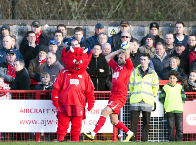 "Crawley Town's David Hunt (centre R) takes a throw on in front of of the team mascot against Bristol City during the FA Cup third round football match at Broadfield Stadium in Crawley on January 7, 2012. Crawley Town won the game 1-0 and advance to the fourth round of the FA cup. AFP PHOTO / ADRIAN DENNIS RESTRICTED TO EDITORIAL USE. No use with unauthorized audio, video, data, fixture lists, club/league logos or ""live"" services. Online in-match use limited to 45 images, no video emulation. No use in betting, games or single club/league/player publications"