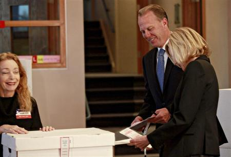 San Diego Republican mayoral candidate Kevin Faulconer (C) casts his vote with his wife Katherine (R) in San Diego, California February 11, 2014. REUTERS/Sandy Huffaker