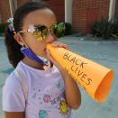 """Bella De La Rosa, 9, holds a paper megaphone up to her mouth at a Black Lives Matter event in Los Angeles on Aug. 2, 2020. """"I want to be louder,"""" Bella told her mother before the racial justice protest. Their solution: a paper megaphone with the words """"Black Lives Matter."""" """"I love to watch her chanting as loud as she can, using her voice,"""" said her mother, Mary De La Rosa. """"It's been a year of her learning to use her voice and to use it proudly."""" (Mary De La Rosa via AP)"""
