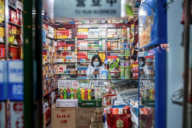A vendor wearing a protective facemask waits for customers at a shop in Beijing