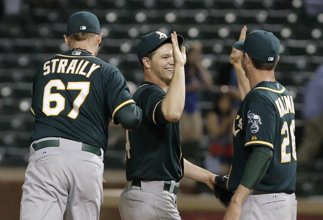 Oakland Athletics starting pitcher Sonny Gray, center, is congratulated by teammates Dan Straily (67) and Scott Kazmir (26) after pitching an entire baseball game against the Texas Rangers, Monday, April 28, 2014, in Arlington, Texas. Oakland won 4-0. (AP Photo/Brandon Wade)