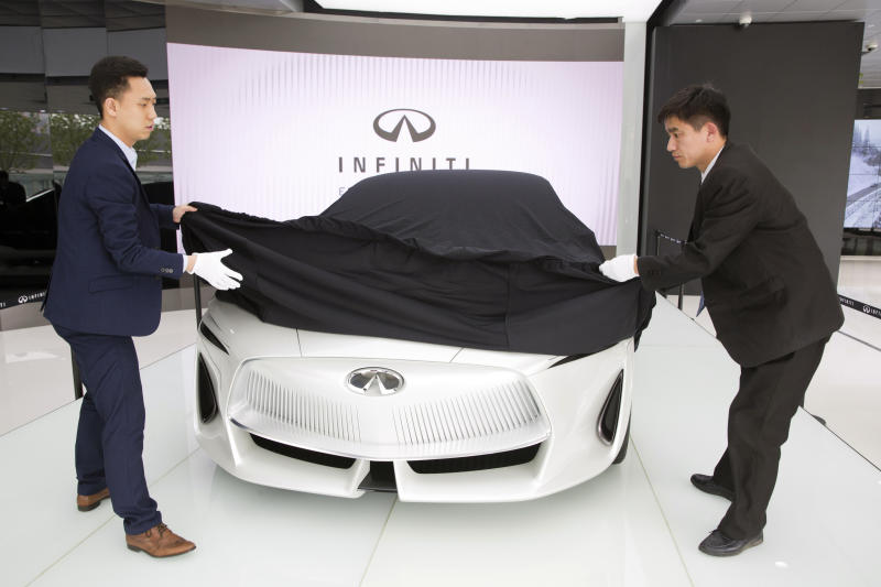 In this April 19, 2018, photo, workers remove the veil from the Infiniti electric concept sedan at a showroom ahead of the Auto China 2018 to be held in Beijing, China. Auto China 2018, the biggest global auto show of the year, showcases China's ambitions to become a leader in electric cars and the industry's multibillion-dollar scramble to roll out models that appeal to price-conscious but demanding Chinese drivers. (AP Photo/Ng Han Guan)