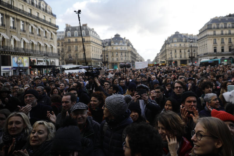 A crowd listens to musicians performing outside the Palais Garnier opera house, Saturday, Jan. 18, 2020 in Paris. As some strikers return to work, with notable improvements for train services that have been severely disrupted for weeks, more radical protesters are trying to keep the movement going. (AP Photo/Kamil Zihnioglu)