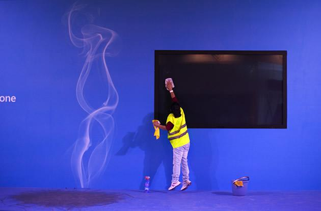 A worker jumps as she cleans a big screen at the start of the world's largest mobile phone trade show.