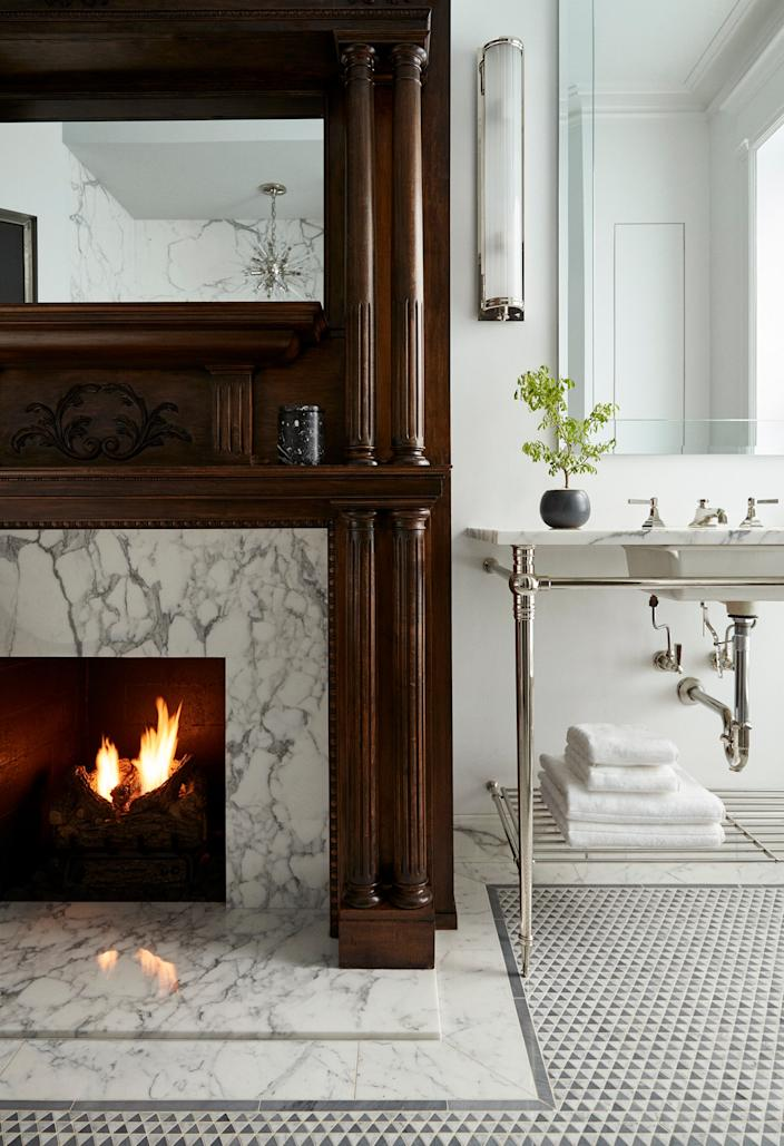 "<div class=""caption""> ""Things we didn't know we really coveted: a fireplace in the bathroom,"" notes Gillian. What was formerly a bedroom on the second floor became the master bath, which has two marble-topped sinks with tapered legs from <a href=""https://sinklegs.com"" rel=""nofollow noopener"" target=""_blank"" data-ylk=""slk:Palmer Industries"" class=""link rapid-noclick-resp"">Palmer Industries</a>. </div>"