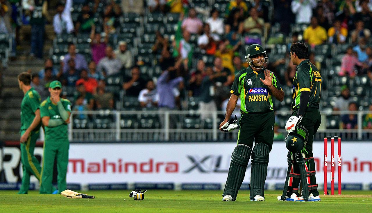 Pakistan's cricketers Mohammad Hafeez (2nd R) and Nasir Jamshed talk during the first T20 cricket match between South Africa and Pakistan at the Wanderers Stadium in Johannesburg on November 20, 2013.  AFP PHOTO / ALEXANDER JOE        (Photo credit should read ALEXANDER JOE/AFP/Getty Images)