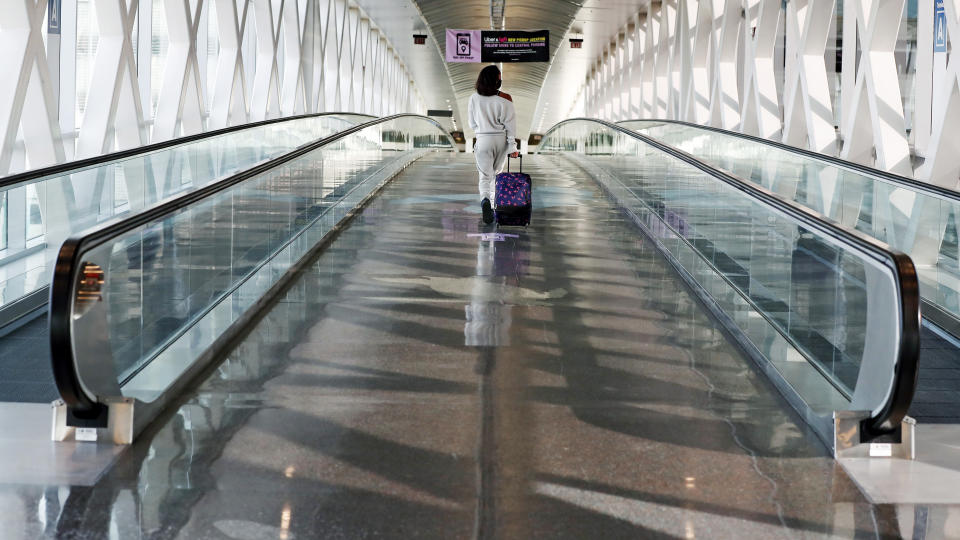 A traveler walks with her luggage across a nearly empty skyway bridge at Logan Airport, Friday Nov. 20, 2020, in Boston. With the coronavirus surging out of control, the nation's top public health agency pleaded with Americans not to travel for Thanksgiving and not to spend the holiday with people from outside their household. (AP Photo/Michael Dwyer)