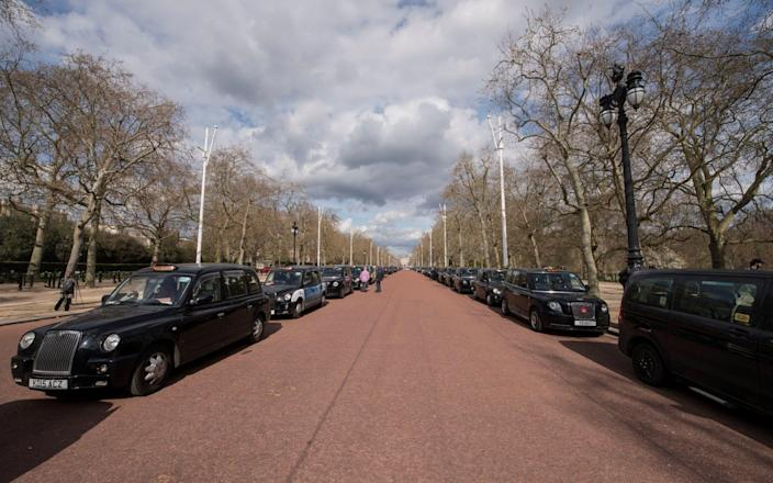 Black London taxi cabs line The Mall near Buckingham Palace - Ian West/PA