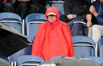 A spectator shields themselves from the rain during day one (Niall Carson/PA Wire)