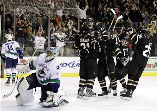 Vancouver Canucks goalie Roberto Luongo (1) lifts himself off the ice as the Dallas Stars celebrate with Loui Eriksson (21), of Sweden, following his goal in overtime to give the Stars the 3-2 win in an NHL hockey game, Sunday, Feb. 26, 2012, in Dallas. (AP Photo/Tony Gutierrez)