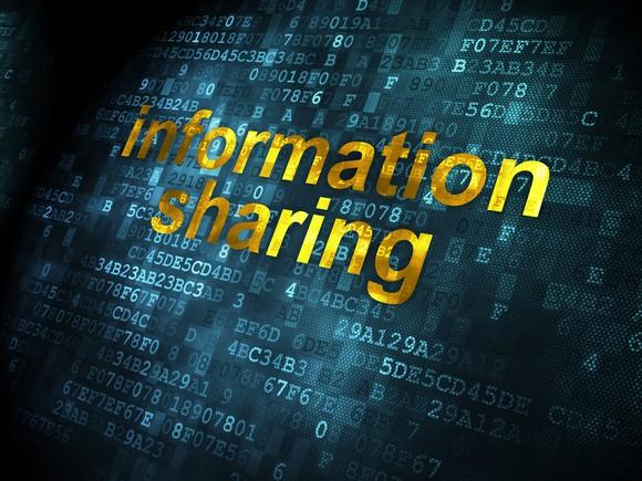 The words information sharing overlaid atop a digital code.