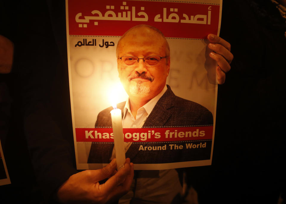 Activists, protesting the killing of Saudi journalist Jamal Khashoggi, hold a candlelight vigil outside Saudi Arabia's consulate in Istanbul, Thursday, Oct. 25, 2018. The poster reads in Arabic:' Khashoggi's Friends Around the World'. (AP Photo/Lefteris Pitarakis)