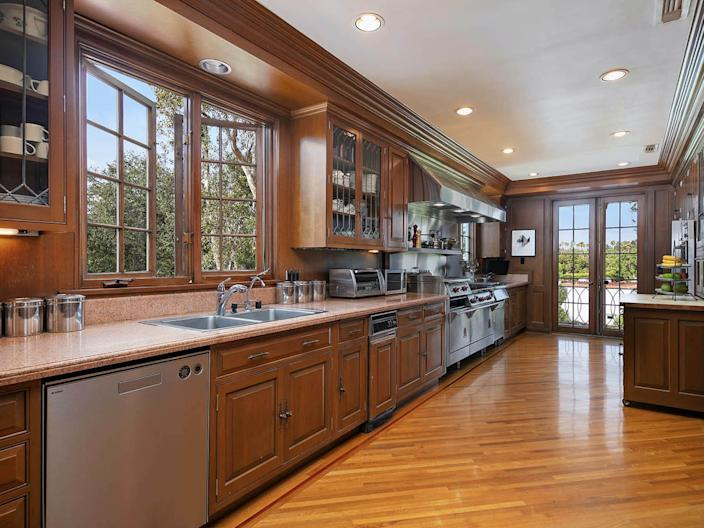 a long kitchen with windows and a glass door at the end