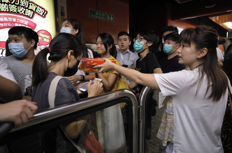 A woman hands a box of biscuits to protesters at a subway station in Hong Kong on Tuesday, July 30, 2019. Protesters in Hong Kong have disrupted subway service during the morning commute by blocking the doors on trains, preventing them from leaving the stations. (AP Photo/Vincent Yu)
