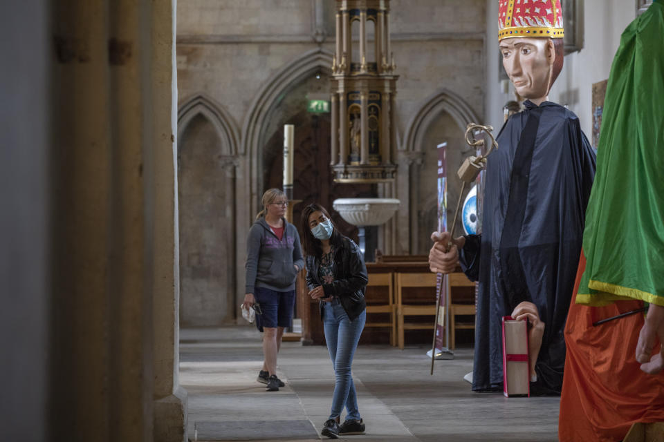 Members of the public look at giant puppets that are part of an annual pilgrimage that was canceled this year due to the coronavirus pandemic, at an exhibit in the nave of St. Albans Cathedral in St. Albans, England, on Thursday, July 2, 2020. The cathedral, one of the largest in England, opened its doors for in-person worship as the government eased coronavirus restrictions. (AP Photo/Elizabeth Dalziel)