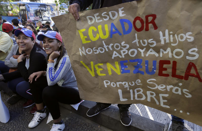"""Venezuelan anti-government protesters gather outside their embassy with a sign that reads in Spanish """"From Ecuador. We, your children, support Venezuela. Because you will be free..."""" in Quito, Ecuador, Wednesday, Jan. 23, 2019. Venezuelan migrants are rallying in favor of Juan Guaido, head of Venezuela's opposition-run congress, who today declared himself interim president of Venezuela. (AP Photo/Dolores Ochoa)"""