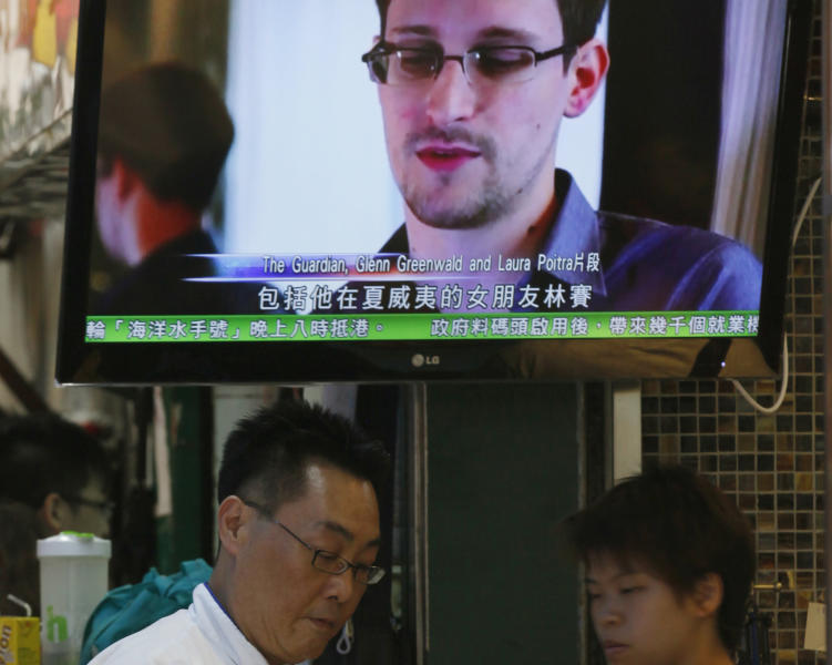 A TV screen shows a news report on Edward Snowden, a former CIA employee who leaked top-secret documents about sweeping U.S. surveillance programs, at a restaurant in Hong Kong Wednesday, June 12, 2013. The whereabouts of Snowden remained unknown Wednesday, two days after he checked out of a Hong Kong hotel. (AP Photo/Kin Cheung)