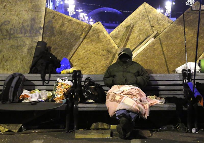 A protester sits next to a barricade in downtown Kiev, Ukraine, early Wednesday, Dec. 4, 2013. Ukraine's opposition failed to force out the government with a parliamentary no-confidence vote Tuesday, leaving political tensions unresolved and a potential standoff between protesters and the country's leaders looming. (AP Photo/Sergei Grits)