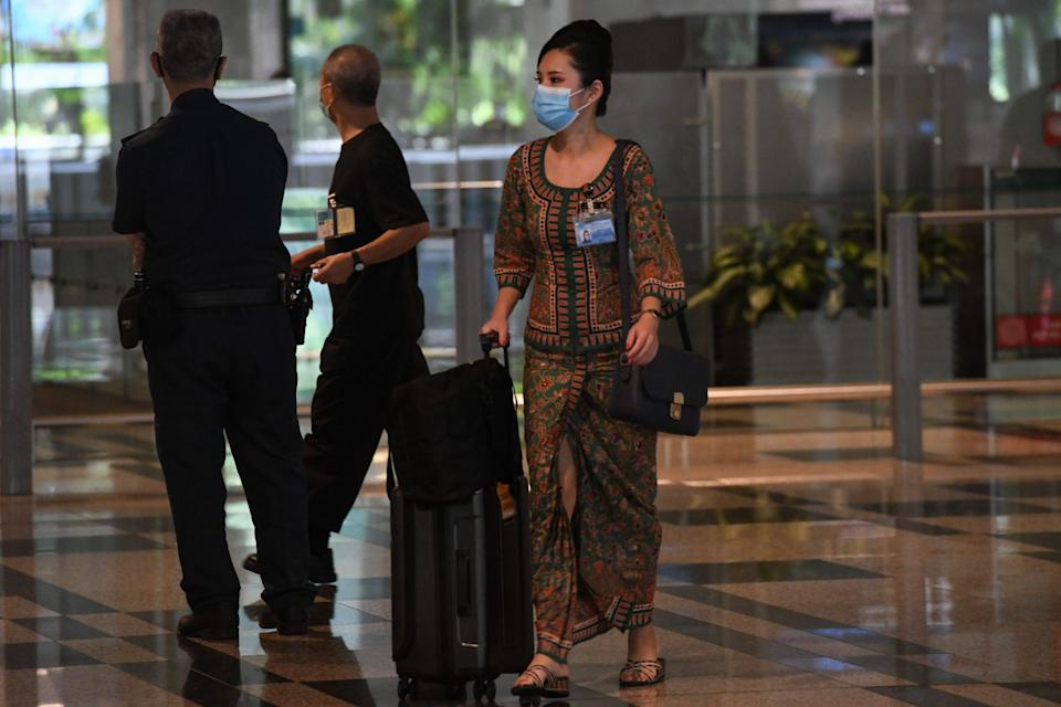 A Singapore Airlines stewardess returns from a flight at Changi International Airport terminal in Singapore on June 8, 2020, as Singapore prepares to reopen its borders after shutting them to curb the spread of the COVID-19 novel coronavirus. (Photo by Roslan RAHMAN / AFP) (Photo by ROSLAN RAHMAN/AFP via Getty Images)