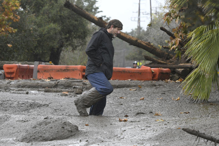 <p>Carpinteria resident Scott Mayfield walks through the mud on Foothill Road in Carpinteria, Calif., Tuesday, Jan. 9, 2018. (Photo: Michael Owen Baker/AP) </p>