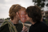 """Shiela Ruiz, right, kisses a photo of President Donald Trump while mingling with Dale Thomas, president of Westlake Village Republican Women Federated, at a boat parade held in support of Trump in Westlake Village, Calif., Friday, Oct. 23, 2020. """"Donald Trump! There is no question,"""" Ruiz said when asked whom she was going to vote for. """"Because he is the man who can lead the country in the way I want to see it led. I have waited for years for a non-politician to run for office."""" (AP Photo/Jae C. Hong)"""