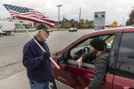 A passing motorist at right argues with Trump supporter Mike Jamerson, left, during a rally at an intersection in Mount Clemens, Mich., Thursday, Oct. 29, 2020. As the traditional Election Day closes in, Americans are exhausted from constant crises, on edge because of volatile political divisions and anxious about what will happen next. (AP Photo/David Goldman)