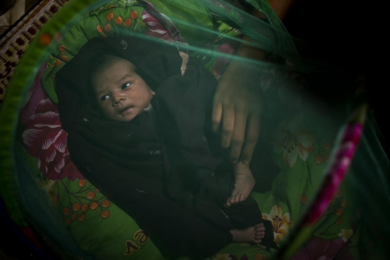 In this Aug. 28, 2012 photo, an HIV-infected mother arranges blankets for her seven-day-old newborn baby under a mosquito net at an HIV/AIDS center on the outskirts of Yangon, Myanmar. The mother will have to wait up to a year and a half to know for sure whether the baby is infected with HIV. Following a half century of military rule, care for HIV/AIDS patients in Myanmar lags behind other countries. Half of the estimated 240,000 people living with the disease are going without treatment and 18,000 are dying from it every year. (AP Photo/Alexander F. Yuan)