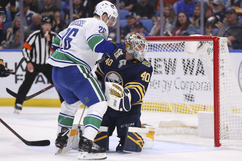 Buffalo Sabres goalie Carter Hutton (40) stops Vancouver Canucks forward Antoine Roussel (26) during the second period of an NHL hockey game Saturday, Jan. 11, 2020, in Buffalo, N.Y. (AP Photo/Jeffrey T. Barnes)