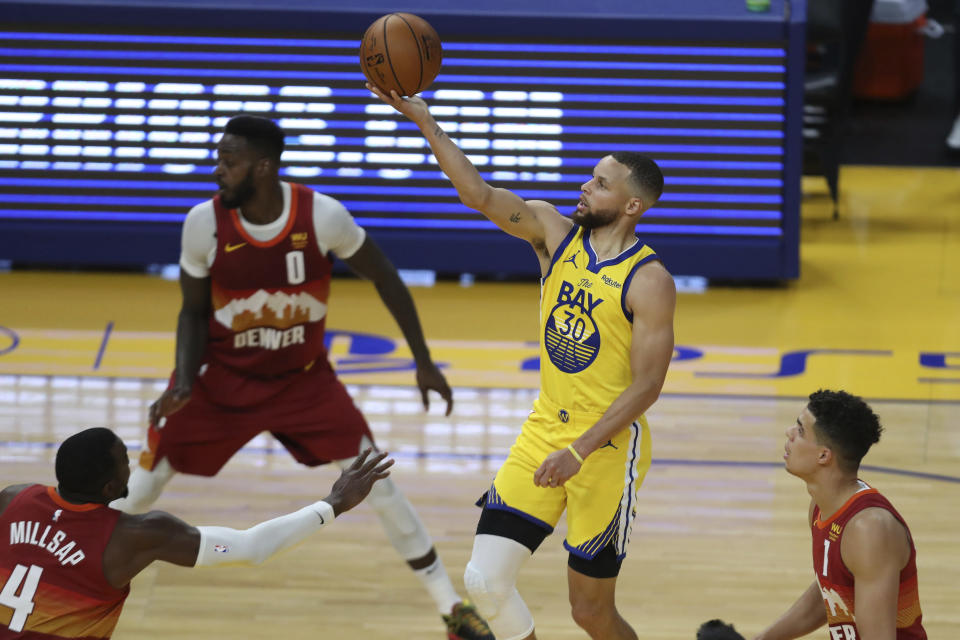 Golden State Warriors' Stephen Curry (30) shoots against Denver Nuggets' Paul Millsap (4) and Michael Porter Jr. (1) during an NBA basketball game in San Francisco, Friday, April 23, 2021. (AP Photo/Jed Jacobsohn)