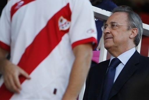 Real Madrid's President, Florentino Perez, right, walks beside a Rayo Vallecano fan during a Spanish La Liga soccer match at the Vallecas stadium in Madrid, Spain, Monday, Sept. 24, 2012. (AP Photo/Andres Kudacki)