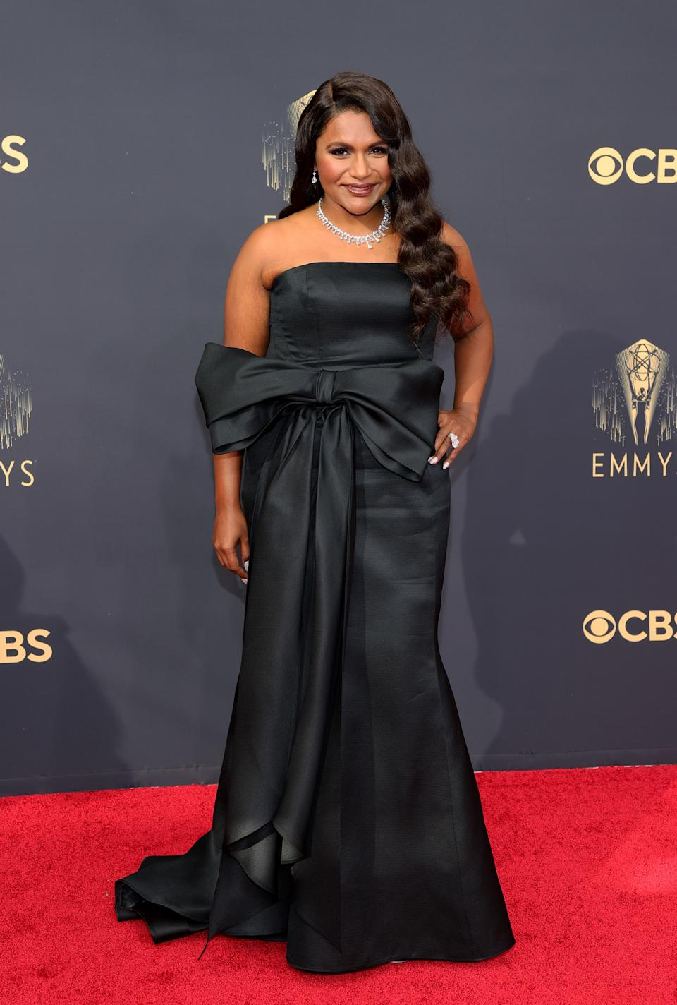Mindy Kaling wears a black strapless dress with a bow at the waist at the 73rd Primetime Emmy Awards at L.A. LIVE on September 19, 2021 in Los Angeles, California. (Photo by Rich Fury/Getty Images)