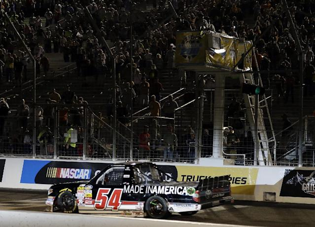 Darrell Wallace Jr. takes the checkered flag to win the NASCAR Truck Series auto race at Gateway Motorsports Park on Saturday, June 14, 2014, in Madison, Ill. (AP Photo/Jeff Roberson)