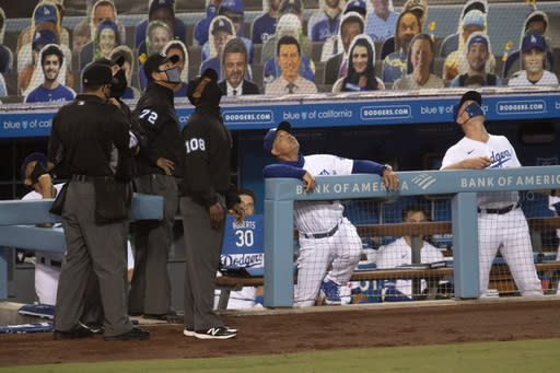 Los Angeles Dodgers manager Dave Roberts, second from right, bench coach Bob Geren, right, and umpires look up as a drone flies over the field during the second inning of a baseball game between the Dodgers and the Colorado Rockies in Los Angeles, Friday, Sept. 4, 2020. (AP Photo/Kyusung Gong)