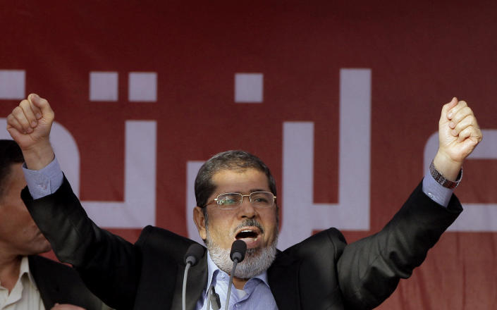 FILE - In this June 29, 2012 file photo, Egypt's then President-elect Mohammed Morsi talks to his supporters at Tahrir Square, in Cairo, Egypt. On Monday June 17, 2019, Egypt's state TV said the country's ousted President Mohammed Morsi, 67, collapsed during a court session and died. It said it occurred while he was attending a court trial on espionage charges. Morsi, who hailed from Egypt's largest Islamist group, the now outlawed Muslim Brotherhood, was elected president in 2012 in the country's first free elections following the ouster the year before of longtime leader Hosni Mubarak. (AP Photo/Amr Nabil, File)