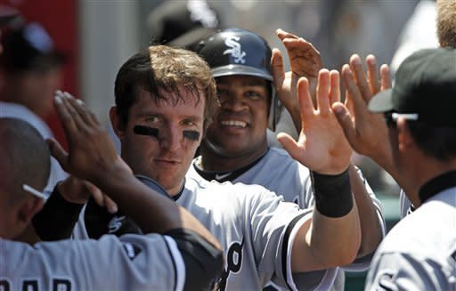 Chicago White Sox's Brent Morel, left, and Dayan Vicedo are congratulated in the dugout after both scored on a single by Adam Dunn in the fourth inning of a baseball game against the Los Angeles Angels, in Anaheim, Calif., Thursday, May 17, 2012. (AP Photo/Reed Saxon)
