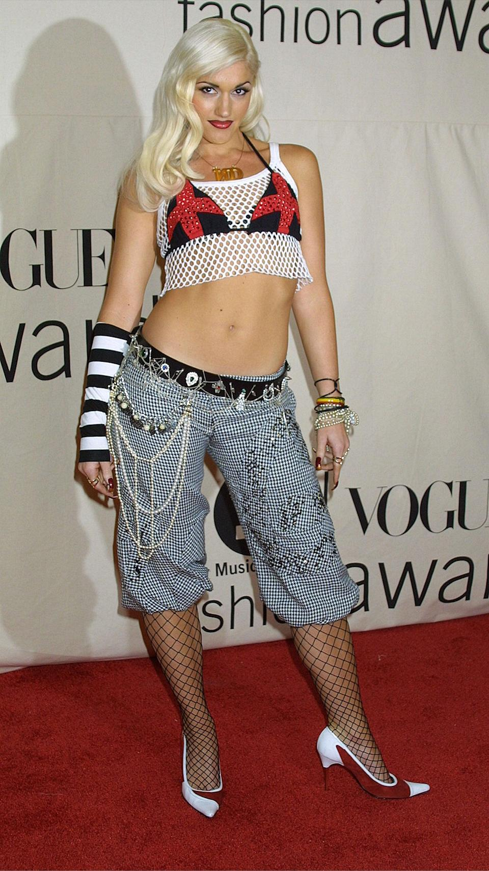 <p>Attending the 2001 VH1/<strong>Vogue</strong> Fashion Awards wearing a fishnet crop top, bikini top, and checkered board shorts.</p>