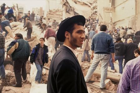 People look on after an explosives-laden truck blew up outside the Argentine Israeli Mutual Association (AMIA) building on July 18 1994, in Buenos Aires