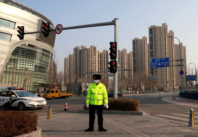 FILE PHOTO: Police guard a blocked-off street in a residential neighbourhood following new cases of the coronavirus disease (COVID-19) in the Tiangongyuan area of Daxing district in Beijing, China