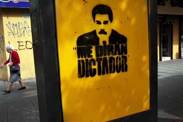 """A woman walks next to a graffiti with the portrait of Venezuela's President Nicolas Maduro and a phrase that reads in Spanish:""""They will call me dictator"""", downtown in Caracas, Venezuela, Thursday, Feb. 20, 2014. After a chaotic and tense night, with gunfire echoing through the streets of many neighborhoods, violence is heating up in Venezuela as an opposition leader faces criminal charges for organizing a rally that set off escalating turmoil in the oil-rich, but economically struggling country. (AP Photo/Rodrigo Abd)"""
