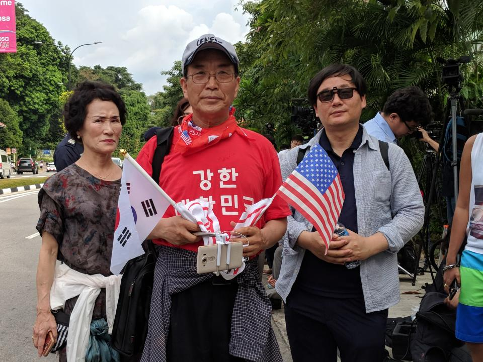 (Three of the four South Koreans who were involved in a protest near Capella on the day of the Trump-Kim summit on 12 June, 2018. They were later advised by the police to disperse. PHOTO: Wong Casandra/Yahoo News Singapore)