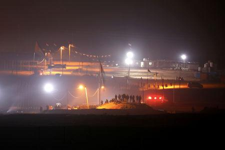 FILE PHOTO: Palestinians stand on a mound during a night protest held along the Gaza side of the border with Israel, as seen from southern Israel March 27, 2019. REUTERS/Amir Cohen/File Photo