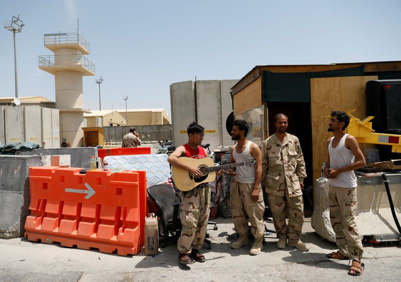 An Afghan soldier plays guitar after it was left by U.S troops in Bagram U.S. air base, after American troops vacated it, in Parwan province