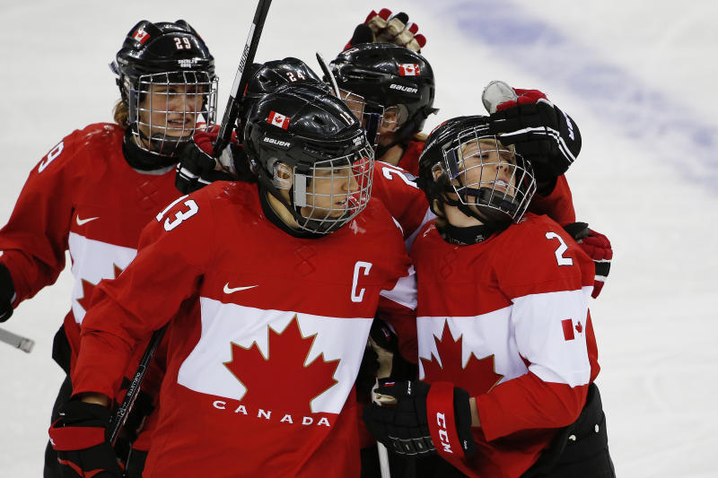Meghan Agosta-Marciano of Canada (2) is congratulated by Caroline Ouellette (13) after scoring a goal against Finland during the third period of the 2014 Winter Olympics women's ice hockey game at Shayba Arena, Monday, Feb. 10, 2014, in Sochi, Russia. (AP Photo/Petr David Josek)
