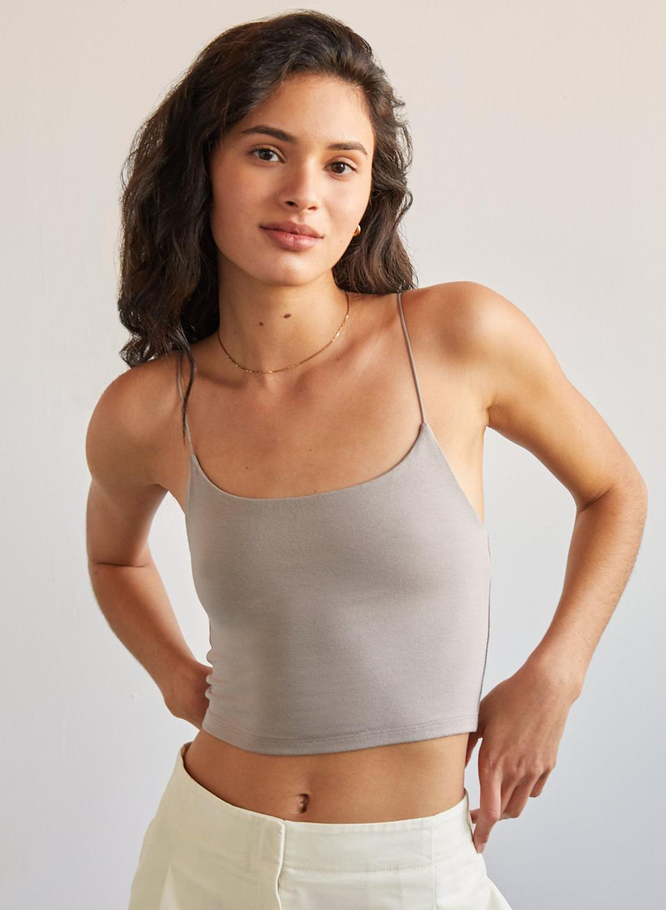 """The skinny lil' spaghetti straps and midriff-baring cut pairs exceptionally well with high-rise pants. Hot take: <a href=""""https://www.huffpost.com/entry/skinny-jeans-canceled-gen-z_l_60256e5cc5b6d667582b6229"""" target=""""_blank"""" rel=""""noopener noreferrer"""">Ain't nothing wrong with those pants being skinny jeans</a>, either!<br /><br /><strong>Promising review</strong>: """"<strong>I LOVE this tank. I have four of them and still want more.</strong>The material is great (it's quite thick) and I love the thin straps. I don't wear a bra with mine and love that the back is cut lower than the front. I wore them all summer with high-waisted shorts/jeans and always felt so cute. Still wear them now during the winter but with baggy knit sweaters."""" —<a href=""""https://go.skimresources.com?id=38395X987171&xs=1&url=https%3A%2F%2Fwww.aritzia.com%2Fus%2Fen%2Fproduct%2Ftiny-tank%2F67652.html"""" target=""""_blank"""" rel=""""nofollow noopener noreferrer"""" data-skimlinks-tracking=""""5876227 xid:fr1621256553293gde"""" data-vars-affiliate=""""www.aritzia.com"""" data-vars-href=""""https://www.aritzia.com/us/en/product/tiny-tank/67652.html?dwvar_67652_color=18255"""" data-vars-keywords=""""fast fashion"""" data-vars-link-id=""""16400690"""" data-vars-price="""""""" data-vars-product-id=""""20980707"""" data-vars-product-img=""""https://aritzia.scene7.com/is/image/Aritzia/large/s21_07_a01_67652_18255_on_a.jpg"""" data-vars-product-title=""""tiny tank Cropped scoop-neck tank"""" data-vars-retailers=""""aritzia"""" data-ml-dynamic=""""true"""" data-ml-dynamic-type=""""sl"""" data-orig-url=""""https://www.aritzia.com/us/en/product/tiny-tank/67652.html?dwvar_67652_color=18255"""" data-ml-id=""""1"""">Kristie P.</a><br /><br /><strong><a href=""""https://go.skimresources.com?id=38395X987171&xs=1&url=https%3A%2F%2Fwww.aritzia.com%2Fus%2Fen%2Fproduct%2Ftiny-tank%2F67652.html"""" target=""""_blank"""" rel=""""noopener noreferrer"""">Get it from Aritzia for$30(available in sizes 2XS–XL and in 11 colors).</a></strong>"""