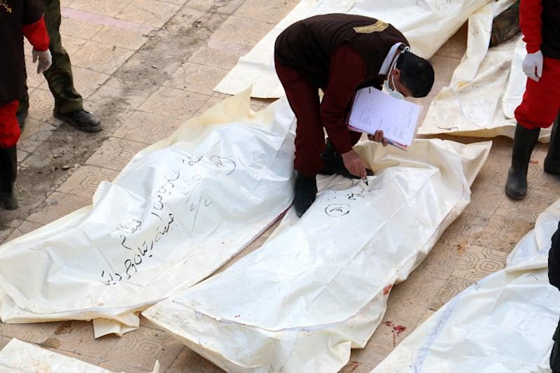 A Syrian emergency personnel inspects reported bodies of Syrian pro-government forces wrapped in plastic bags on February 23, 2015, in the rebel-held side of the northern Syrian city of Aleppo (AFP Photo/Zein Al-Rifai)