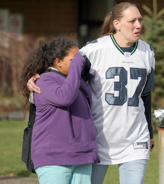 Armin Jahr Elementary School fourth grade student Honesty Hubbard, 9, wipes away tears as she is escorted by her mom, Jennifer Barber, from the school on Wednesday, Feb. 22, 2012, in Bremerton, Wash. An 8-year-old girl was shot in the abdomen at the elementary school and one of her classmates was detained, authorities said. The injured third-grader was airlifted to Seattle's Harborview Medical Center. Authorities said a third-grade boy was being questioned and a firearm was found in a classroom. (AP Photo/Kitsap Sun, Larry Steagall)